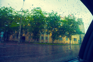 Driving in rain. Unfocused view of Tallinn. Focus on raindrops on the window