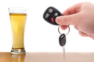 Drunk driving concept image with a hand holding some car keys and a glass of beer isolated over a white background.