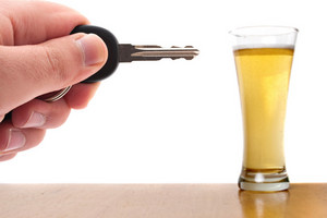 Drunk driving conceptual image with a hand holding some car keys and a glass of beer in the background.  Shallow depth of field.