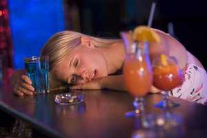 Drunk young woman resting head on bar counter
