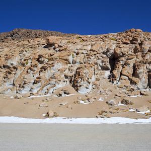 Dry road past rocky cliffs under a blue sky