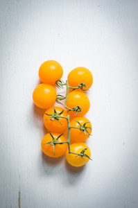 Yellow Tomatoes On The Vine On Wooden Background