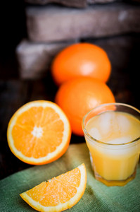 Glass Of Orange Juice With Ice And Sliced Oranges On Wooden Background