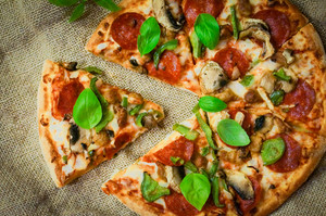 Sliced Home Made Pepperoni Pizza On Wooden Rustic Background