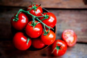 Tomates na cesta no fundo de madeira