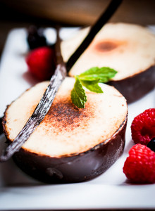 Creme Brulee With Vanilla Sticks And Berries On Wooden Background
