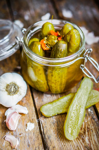 Pickles With Garlic In Glass Jar On Rustic Wooden Background