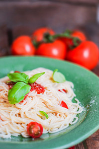 Spaghetti With Tomatoes And Basil On Wooden Background