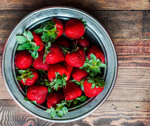 Strawberries In A Bowl On Wooden Background