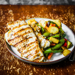 Grilled Chicken With Baked Vegetables On Rustic Background