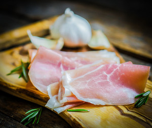 Prosciutto With Garlic And Rosemary On Rustic Wooden Background