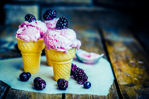 Ice Cream In Cones With Berries On Rustic Wooden Background