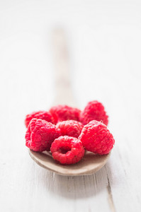 Raspberries In Wooden Spoon On White Background