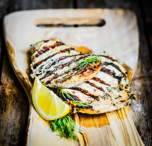 Grilled Chicken With Herbs And Lemon On Wooden Background