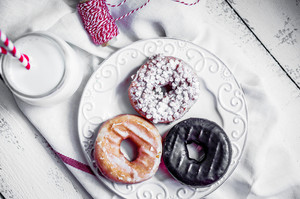 Milk And Assorted Donuts On Rustic Wooden Background