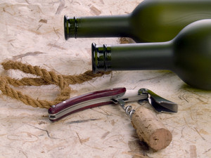 Dull Vine Bottles And Corkscrew On The Natural Background