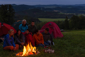 During night camping friends setting fire beside tents