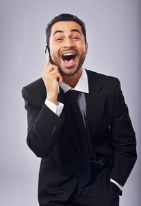 Ecstatic businessman with a cell phone excited about a good news