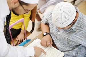 Education activities in classroom at school, Muslim teacher showing Koran to kid