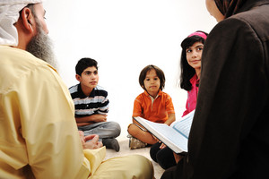 Education activity in Ramadan, Muslim couple and children reading Koran