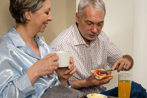 Elderly couple eating romantic breakfast together in bed