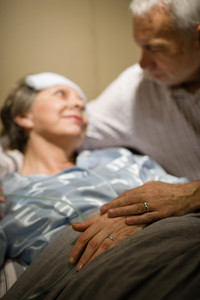 Elderly couple holding hands at clinic ward bed