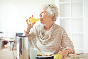 Elderly woman drinking a glass of orange juice