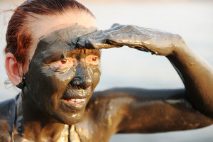 Elderly woman in a bathing suit of natural mineral mud sourced from the dead sea in Jordan