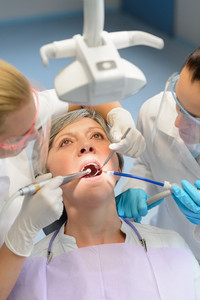 Elderly woman patient open mouth dental checkup professional dentist team