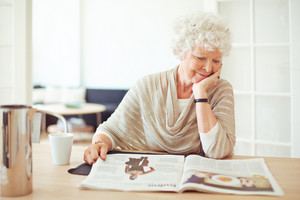 Elegant grandmother sitting at home reading a magazine