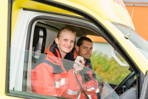 Emergency paramedic in ambulance car talk radio smiling confident