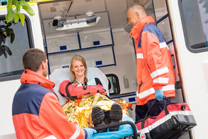 Emergency paramedics with injured woman in ambulance on stretcher
