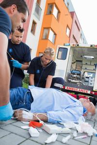 Emergency team examining injured senior patient lying on street