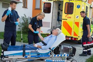 Emergency team examining injured senior patient lying on stretcher outdoors