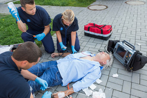 Emergency team giving firstaid to injured elderly patient on street