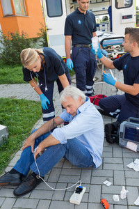 Emergency team giving help to senior man sitting on street