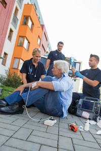 Emergency team helping injured elderly patient sitting on street