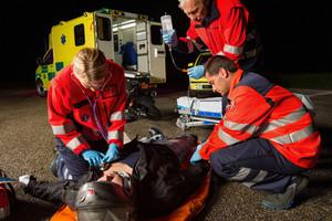 Emergency team helping injured motorbike man driver at night