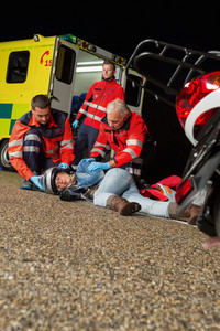 Emergency team helping injured motorbike woman driver at night