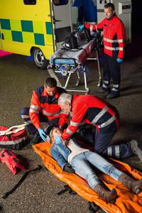 Emergency team helping injured motorcycle woman driver at night