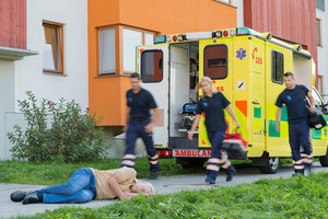 Emergency team running to unconscious senior man lying on street