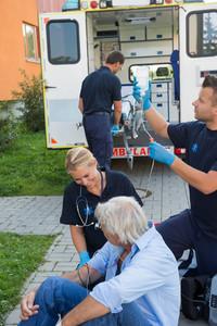 Emergency team treating injured senior patient sitting on street