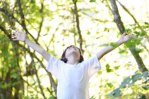 Enjoying the nature. Cute little boy with arms raised enjoying the fresh air in green forest.