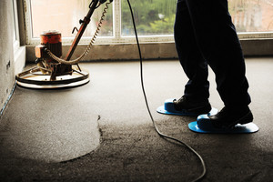Equating and leveling fresh cement for the floor, by one worker