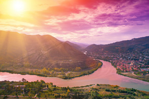 Evening panoramic view of Mtskheta city and Kura river from Jvari monastery at sunset. Georgia country