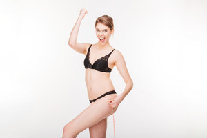 Excited happy young woman in black lingerie celebrating success and measuring her hips