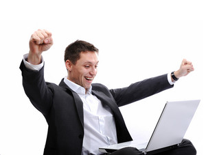 Excited man using laptop with arms up in the air