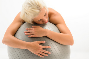 Exhausted sport woman resting on fitness ball on white background