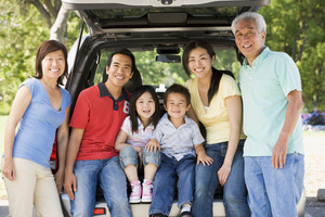 Extended family sitting in tailgate of car