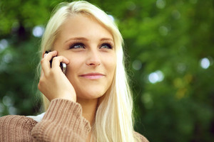 Face of radiant young blonde woman with an amused expression on her mobile phone against green foliage.